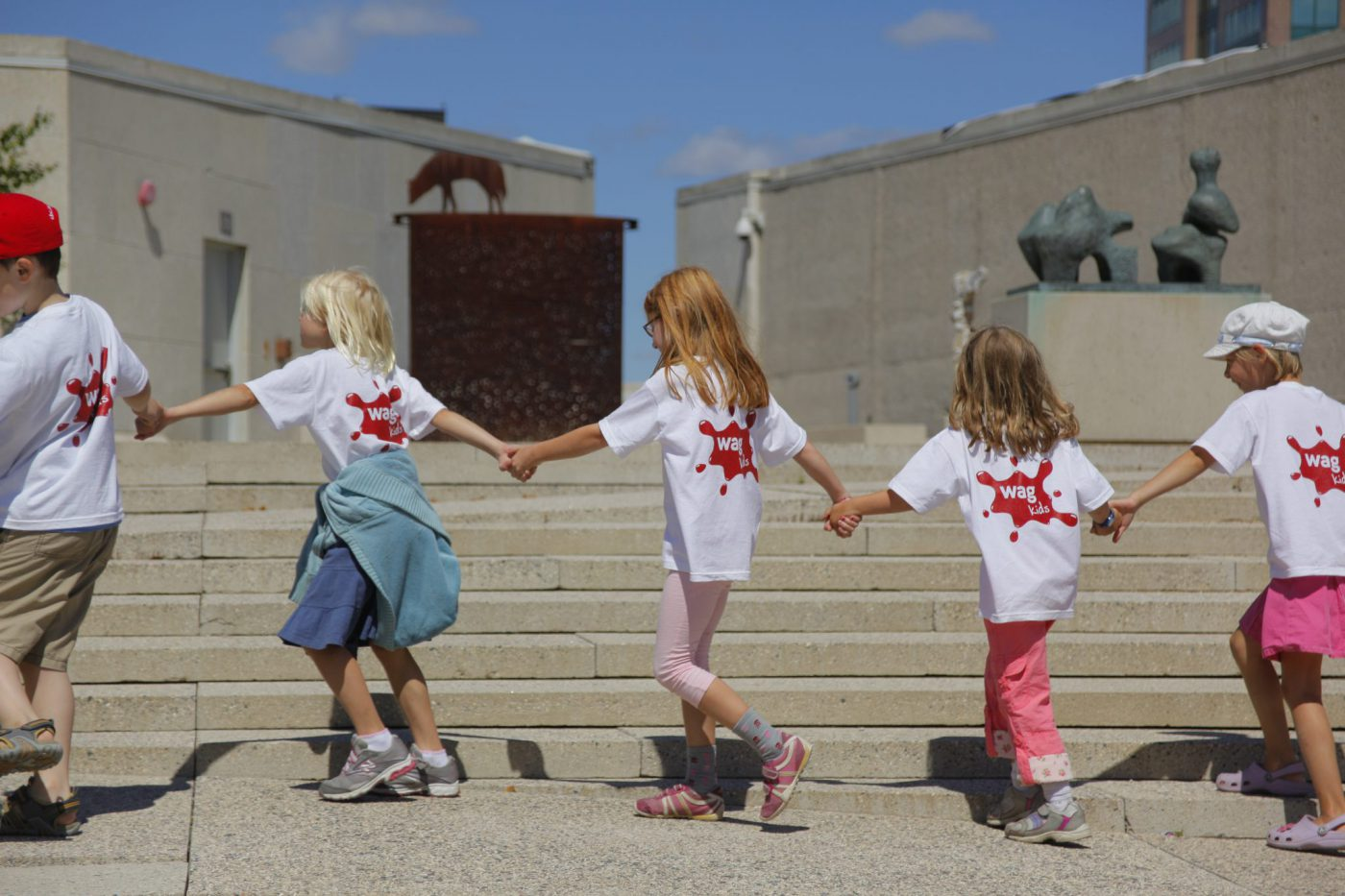 Kids at a WAG Art Camp holding hands while walking in a line.