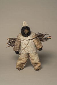 Unidentified artist (Canadian (Hopedale), 20th century). Woman Dressed in Caribou Skin Clothing, 1975–1976, caribou skin, wood, sealskin, wood, cotton, embroidery floss, fake fur, 47 x 40.5 x 15 cm. Collection of the Winnipeg Art Gallery. Gift of JoAnn and Barnett Richling, 2013-108. Photograph: Ernest Mayer, courtesy of the Winnipeg Art Gallery.