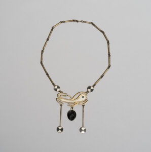 Annie Manning. Inuit (Kinngait), b. 1943. Necklace, 1976. brass, stone (soapstone), ivory. Government of Nunavut Fine Art Collection. On long-term loan to the WAG, 2.77.21
